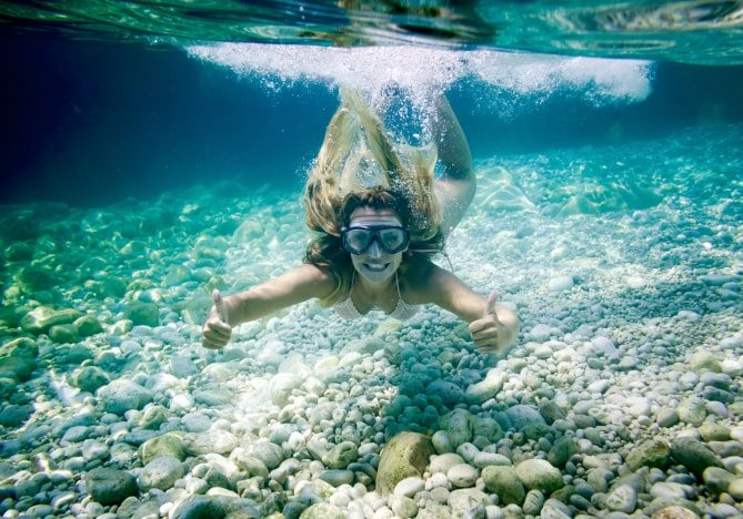snorkeling-in-the-tropical-sea-woman-shows-thumb-u-LAF7S5D-min